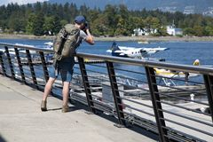 Young man backpack taking pictures ocean. Male traveller photographer water planes deck Vancouver waterfront Stock Images