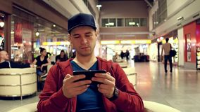 Male traveller in red playing a game on his mobile phone at the airport cafe. 4K shot. Male traveller in red playing a game on his mobile phone at the airport stock footage