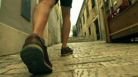 Male traveller`s feet, back view. Walking along ancient Mediterranian city street. Traveller`s feet. Walking along ancient Mediterranian city street Royalty Free Stock Images
