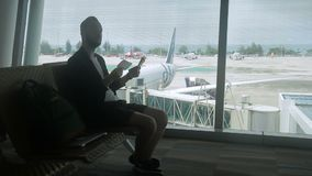 Male traveller is waiting for his flight in the airport. Man is sitting on comfortable chair near the window with view to airside and planes and checking his stock video