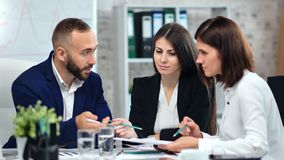 Male trendy boss in suit discussing project with two female employee at modern office interior. Medium shot. Business people having team meeting talking stock footage