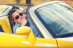 Male trendy model posing. In yellow convertible car. Sunglasses. checkered shirt Royalty Free Stock Images