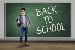 Male trendy student back to school. Happy male student celebrate back to school in the classroom while carrying backpack and books Royalty Free Stock Images