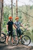 male trial bikers in helmets with mountain cycles resting with sport bottles of water near river stock photos