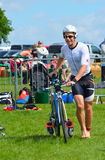 Male triathlete at end of cycling stage with bicycle. Grafham, Cambridgeshire, England - May 22, 2016: Male triathlete at end of cycling stage with bicycle Stock Photos