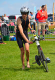Male triathlete at end of cycling stage with bicycle. Grafham, Cambridgeshire, England - May 22, 2016: Male triathlete at end of cycling stage with bicycle Stock Image