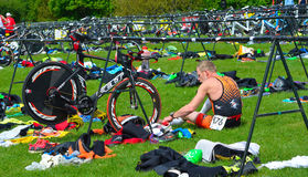 Male triathlete at end of cycling stage sitting on the ground with bicycles. Grafham, Cambridgeshire, England - May 22, 2016: Male triathlete at end of cycling Royalty Free Stock Image