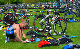 Male triathlete at end of cycling stage sitting on the ground with bicycles. Grafham, Cambridgeshire, England - May 22, 2016: Male triathlete at end of cycling Stock Images