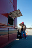Male truck driver calling for help via cell phone. Photo shows burgundy tractor with side box tool compartment open, truck driver wearing red cap, blue jeans and Royalty Free Stock Photography
