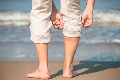Male tucks linen trousers. On the beach Stock Image