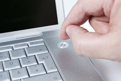 Male turning on a laptop. Picture shows the activation from a power switch Royalty Free Stock Images