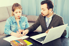 Male tutor assisting his teenage pupil to prepare for test. Adult spanish  male tutor assisting his teenage pupil to prepare for test Royalty Free Stock Photo
