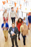 Male Tutor In Classroom Surrounded By Moving Students Stock Image