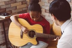 Male tutor teaching black girl to play guitar stock images