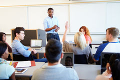 Male Tutor Teaching University Students In Classroom Stock Photo
