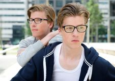 Male twin fashion models. Close up portrait of male twin fashion models with glasses posing outdoors Royalty Free Stock Image