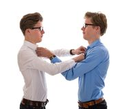 Male twins correcting each other clothes. Isolated at white Stock Photography