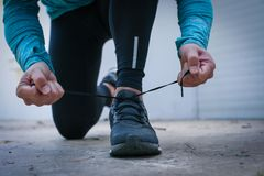 Male tying snickers. Close up. Male tying snickers. Sporty man on road city tying sports shoes Royalty Free Stock Image