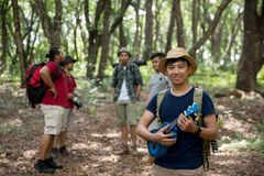 Male with ukulele hiking to the forest. Asian male with ukulele hiking to the forest with friends Stock Image
