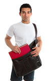 Male University College Student. A casually dressed male placing a textbook into a leather satchel bag.  White background Royalty Free Stock Photos