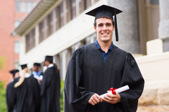 Male university graduate. Cheerful young male university graduate in front of school building Royalty Free Stock Photography