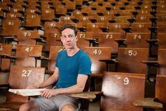 Male University Student. Portrait of a young university student sitting in a lecture hall Stock Image