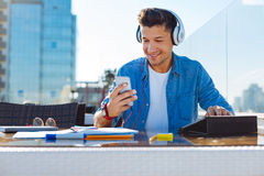 Male university student in casual listening to music. Inspired and ready to work. Low angle view on a relaxed young man wearing headphones enjoying the music Royalty Free Stock Image