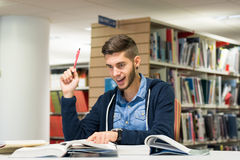 Male university student in the library. Male student in the library doing research and finding the answer. Studying for exam Stock Photography