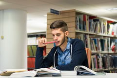 Male university student in the library. Good looking male student reading and doing research in the library. Studying for exam Royalty Free Stock Image