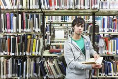 Male University Student In Library. Portrait of a young male university student against bookshelf in library Royalty Free Stock Images
