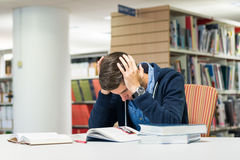 Male university student in the library. Male student in the library trying to study being stressed and panicking over exam Royalty Free Stock Image