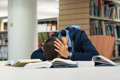 Male university student in the library. Male student in the library trying to study being stressed and panicking over exam Royalty Free Stock Images