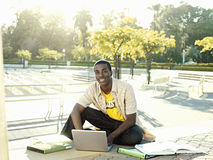 Male university student sitting on ground with textbooks, using laptop, smiling, portrait Royalty Free Stock Photos
