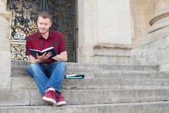Male University Student Sitting On Steps And Reading Outside Bui. Male University Student Sits On Steps And Reading Outside Building Stock Photos