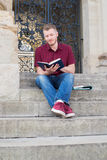 Male University Student Sitting On Steps And Reading Outside Bui. Male University Student Sits On Steps And Reading Outside Building Royalty Free Stock Image