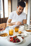 Male� up tea with spoon. Young couple having breakfast together and male� tea up with spoon Royalty Free Stock Photo