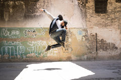 Male urban dancer in the air. Good looking male hip hop dancer jumping and performing in an abandoned building with graffiti walls Royalty Free Stock Photography