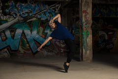 Male urban dancer standing on his toes. Full length view of a young male urban dancer standing on his toes while dancing in an abandoned building Royalty Free Stock Image