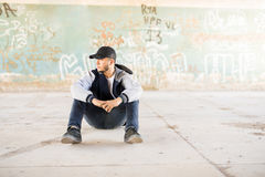 Male urban dancer taking a break. Good looking male urban dancer sitting outdoors in an urban setting with graffiti walls. Lots of copy space Royalty Free Stock Photo