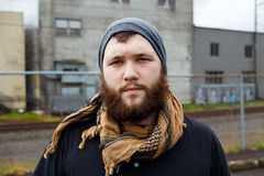 Male Urban Lifestyle Portrait. Young adult man outdoors in an urban environment for a lifestyle portrait of a bearded hipster Royalty Free Stock Image