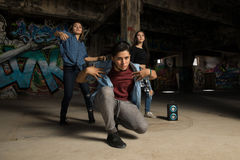 Male urban rapper with a couple of girls. Portrait of a handsome young rapper dancing and singing with a couple of girls in an urban setting Stock Image
