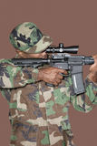 Male US Marine Corps soldier aiming M4 assault rifle over brown background royalty free stock photo