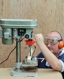 male using a drill press on wood Royalty Free Stock Image