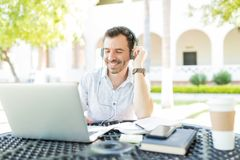 Male Using Headphones Connected To Laptop While Telecommuting In. Smiling mid adult male using headphones connected to laptop while telecommuting in garden stock photo