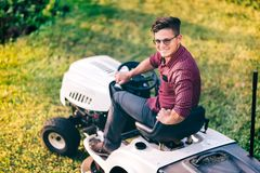Male using industrial lawn mower and cutting grass. Portrait of male using industrial lawn mower and cutting grass Royalty Free Stock Image
