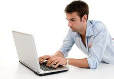 Male Using Laptop. Male Relaxing On Floor Using Laptop Computer Stock Photos