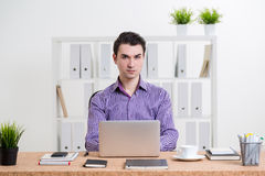 Male using laptop. Caucasian businessman in striped purple shirt using laptop placed on office desktop and looking at the camera Stock Photography