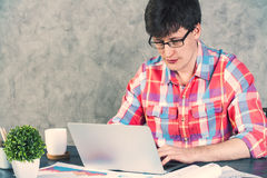 Male using laptop concrete. Caucasian male using laptop on office desk with items. Concrete wall background Stock Photography