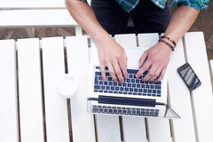 Male using laptop. Looking down on male using laptop on white table Stock Image