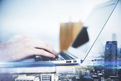 Male using laptop. Side view of male hands using laptop on city background. Double exposure. Filtered image Stock Photography